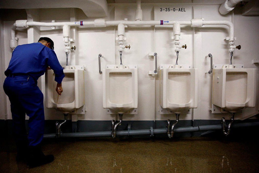 一名船員仔細刷洗小便斗。 (路透)
