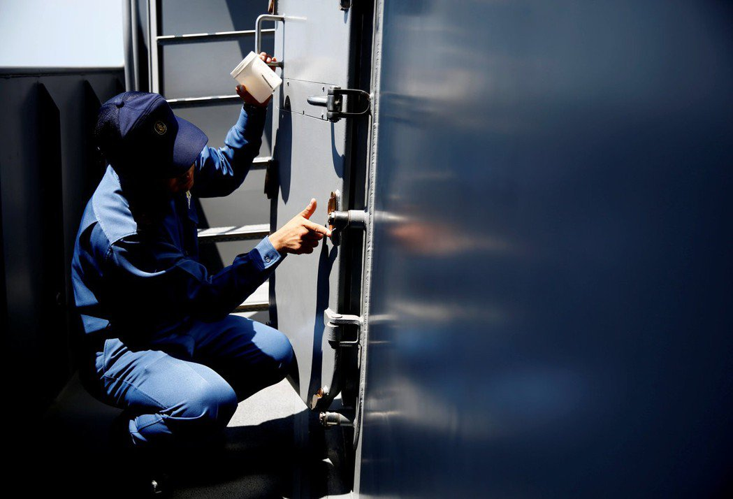 一名船員正在為銅質把手塗上凡士林防鏽。 (路透)