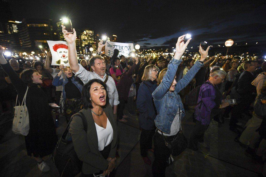抗議民眾拿出手機的閃光燈和手電筒,試圖在廣告播放時用燈光干擾。 圖/美聯社