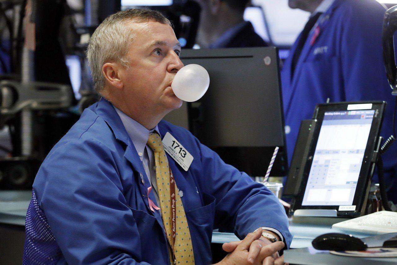 美股前晚崩跌八百多點,昨天引爆全球股災。圖為紐約證交所營業員邊看大盤、邊吹泡泡。...