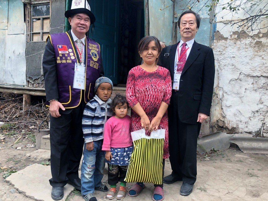 蕭文龍(左一)與認養兒童家庭相見歡。 富偉獅子會/提供