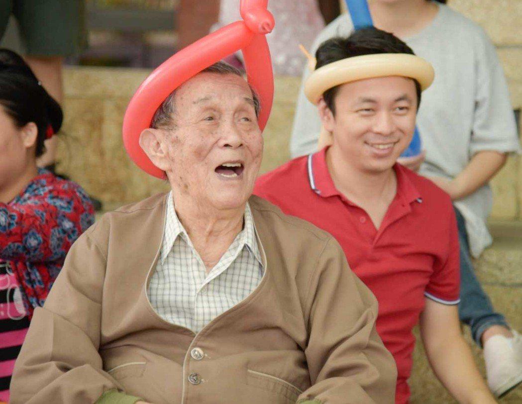 90歲周爺爺跟著小丑爺爺做氣球健康操玩得不亦樂乎,坐在身後在裕隆格上租車服務的兒...