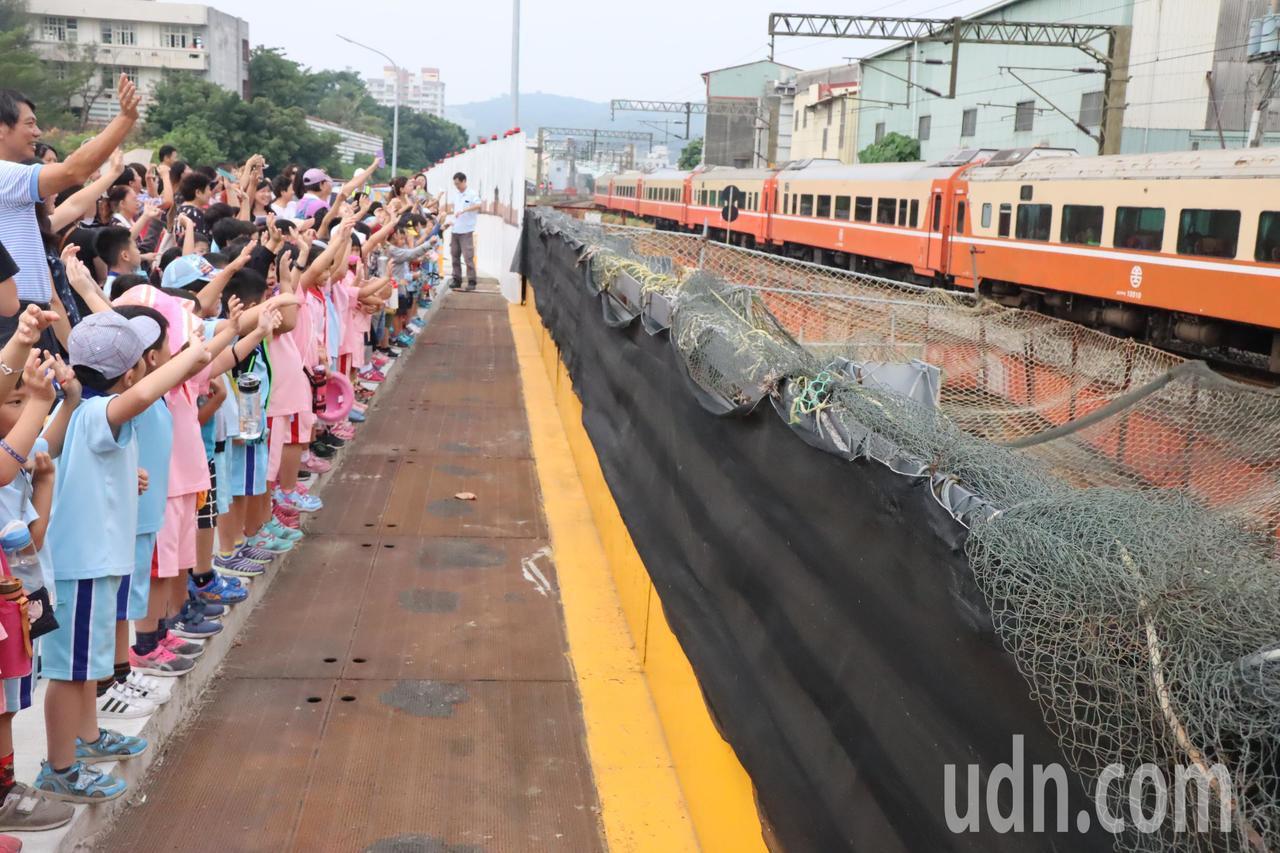「再見!再見!」三民國小學童揮著小手向駛過的火車告別,高雄市區鐵路地下化後,校園...