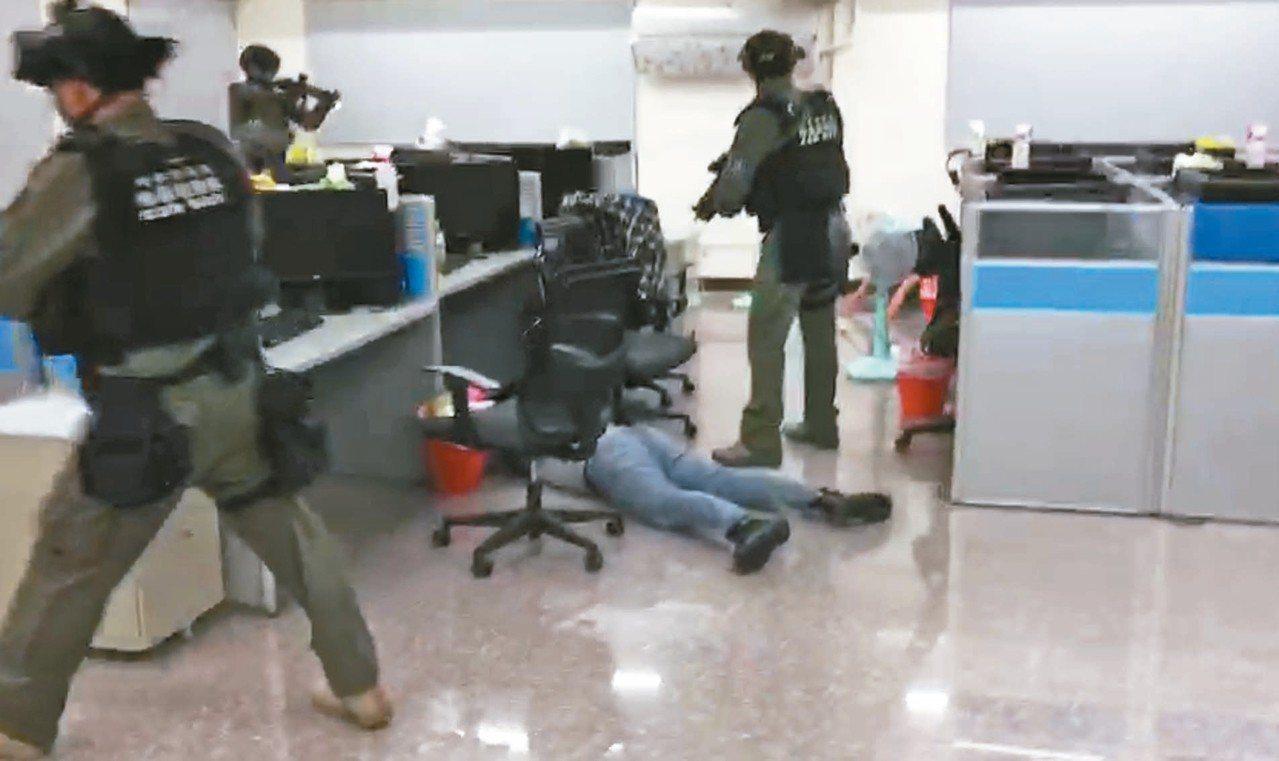 台灣警方前天在台中市區破獲詐騙集團,持槍喝令在場人等全都趴下。 記者李承穎/翻攝