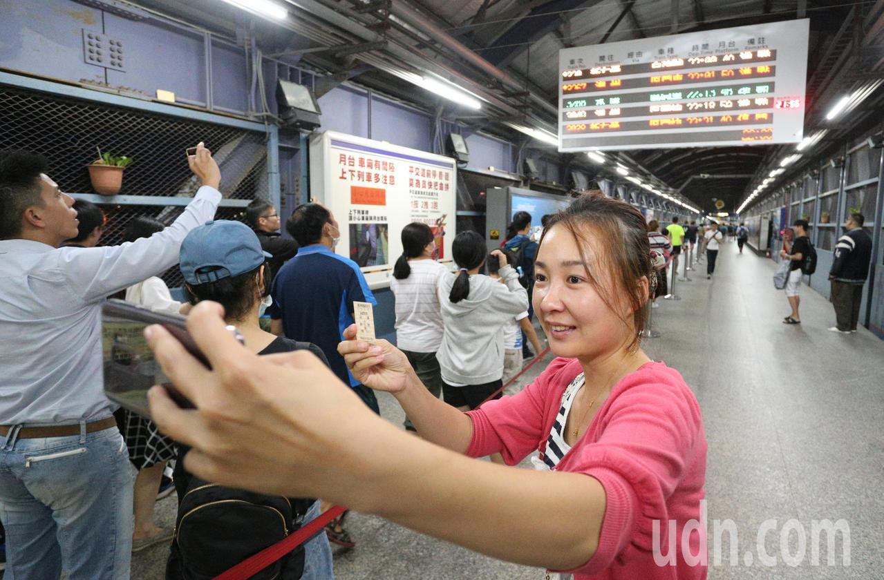 一名民眾拿起紀念車票在電子看板前拍照留念。記者劉學聖/攝影