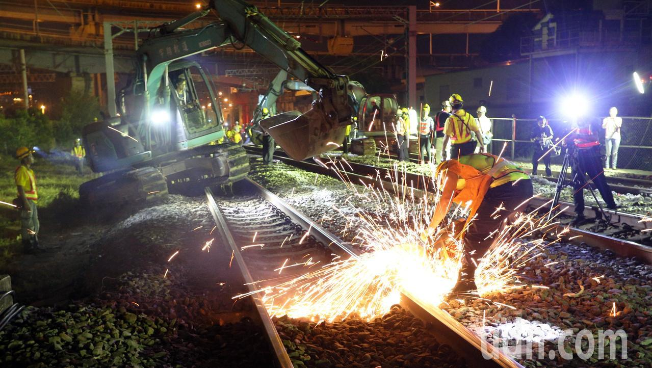 台鐵工程人員加班整備進行左營地下化軌道切換作業,一名工人進行軌道切除作業,冒出大...