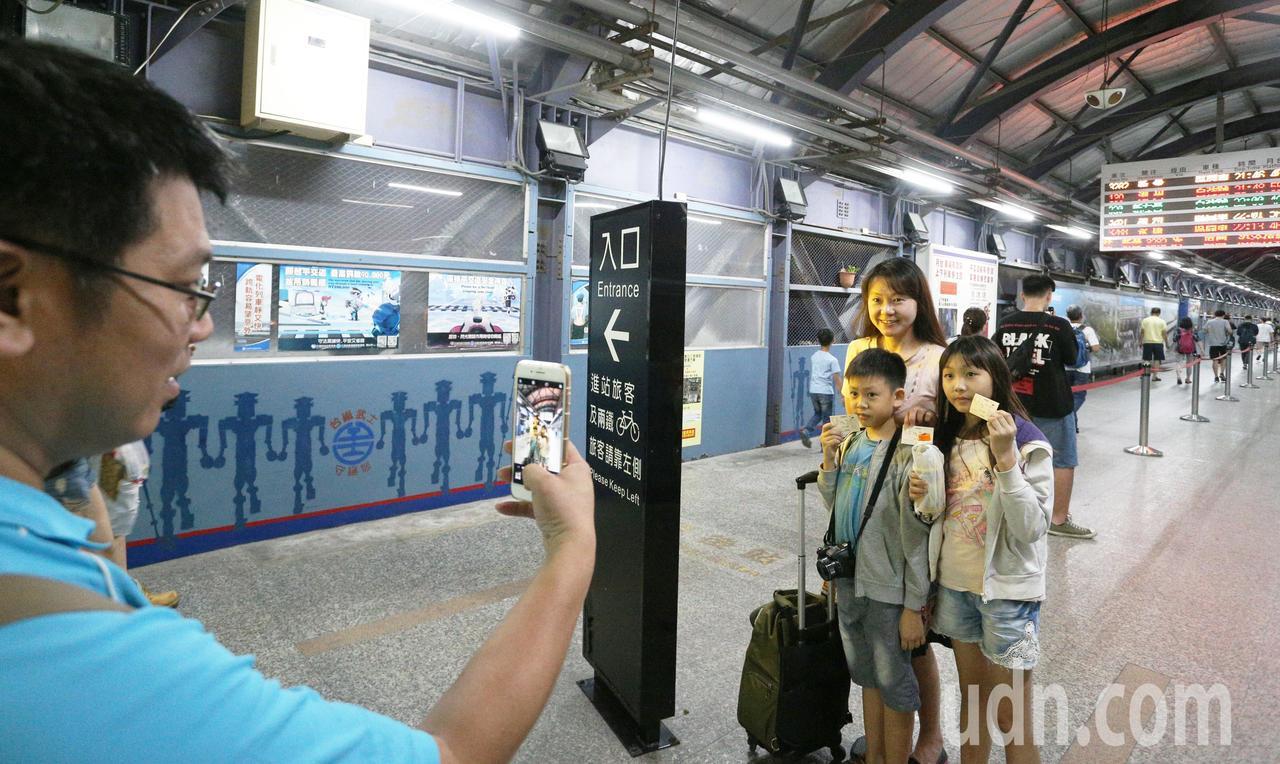 民眾拿起紀念車票在電子看板前拍照留念。記者劉學聖/攝影