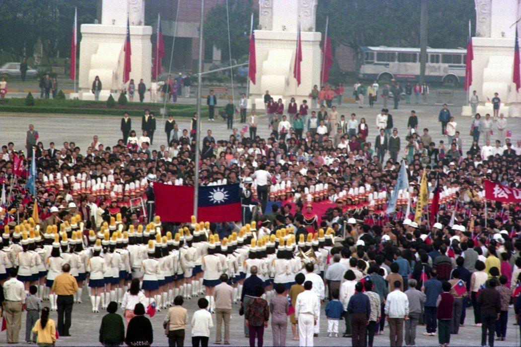1990年在中正紀念堂舉行升旗活動,民眾肅立齊唱國歌。 圖/聯合報系資料照片