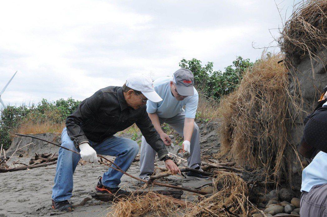 精密機械協會理事長許文憲(右)與程泰集團董事長楊德華(左)合力移除海灘漂流木。 ...