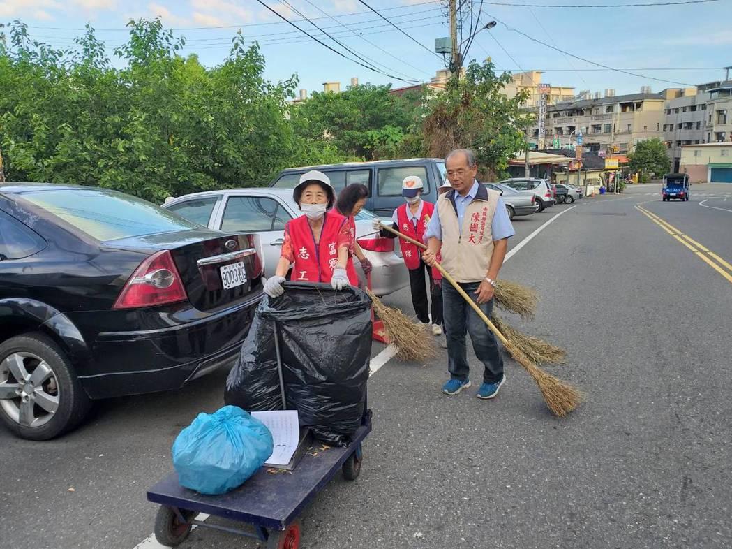 南投縣議員候選人陳國大(右)帶著環保志工,在草屯鎮的社區掃馬路。 圖/陳國大提供