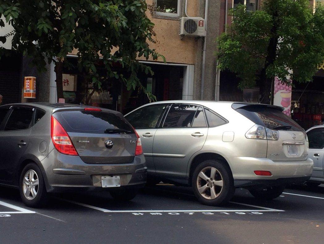 一個停車位硬要擠進兩輛車,結果是兩輛車都會被開停車收費單。 記者徐如宜/攝影