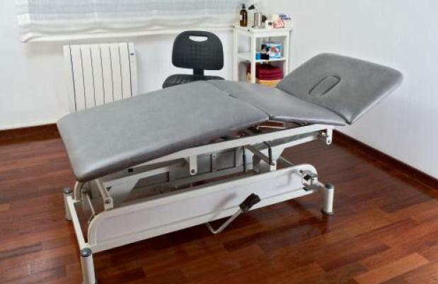 運動機構內的按摩空間。圖中可見一張油壓三段式的按摩床。治療師的椅子有輪子,另外還...
