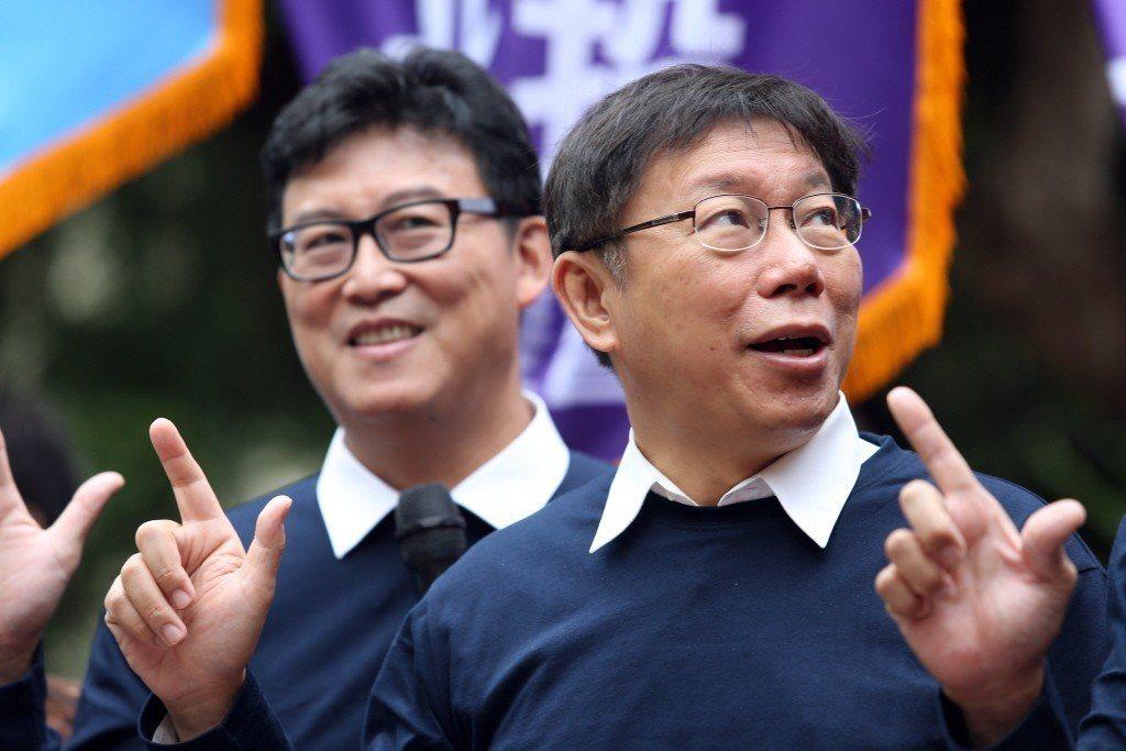 2014年,台北市長候選人柯文哲(右)與支持者一同比出「七號」手勢高喊「凍蒜」。...