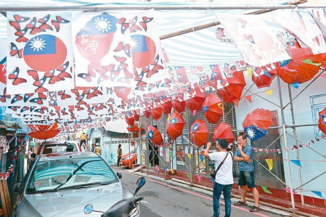 桃園市大溪區仁義里,日前搜集廢棄雨傘、寶特瓶、安全帽等,以紅、藍色油漆,畫出國旗...