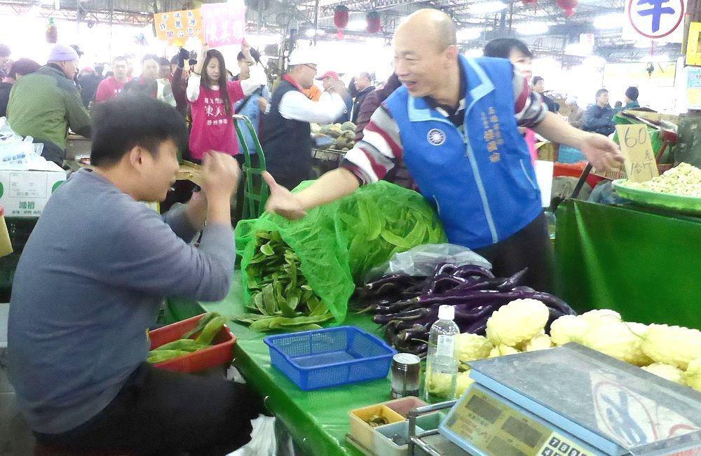 韓國瑜(右)曾任北農總經理,綠營曾抨他「菜蟲」,他拿此事提醒支持者留意選舉花招。...