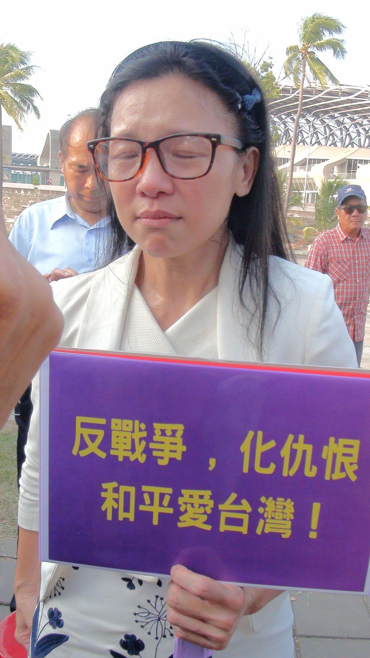 無黨籍高雄市長候選人璩美鳳舉著「反戰爭.化仇恨.和平愛台灣!」標語出現在民進黨的...