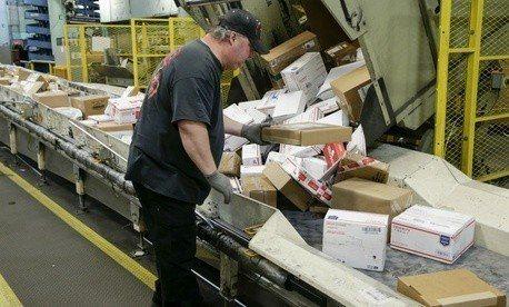 美國宣布自17日啟動退出萬國郵政聯盟程序。圖為美國快遞業員工正在處理包裹。(美聯...