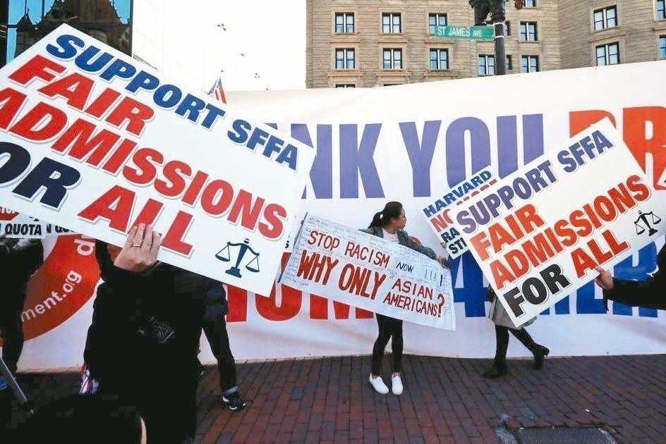 民眾高舉標語牌與布條,呼籲哈佛公平對待各族裔學生。(路透)