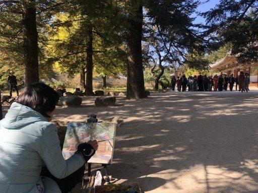 北韓妙香山高麗時期的寺廟「普賢寺」內,北韓學生席地而坐繪畫。 記者侯俐安/攝影