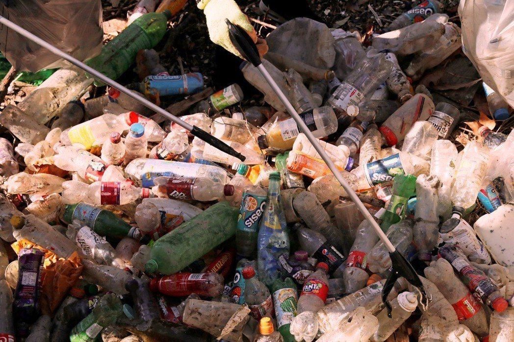 英國民眾在泰晤士河岸清理垃圾。圖/美聯社