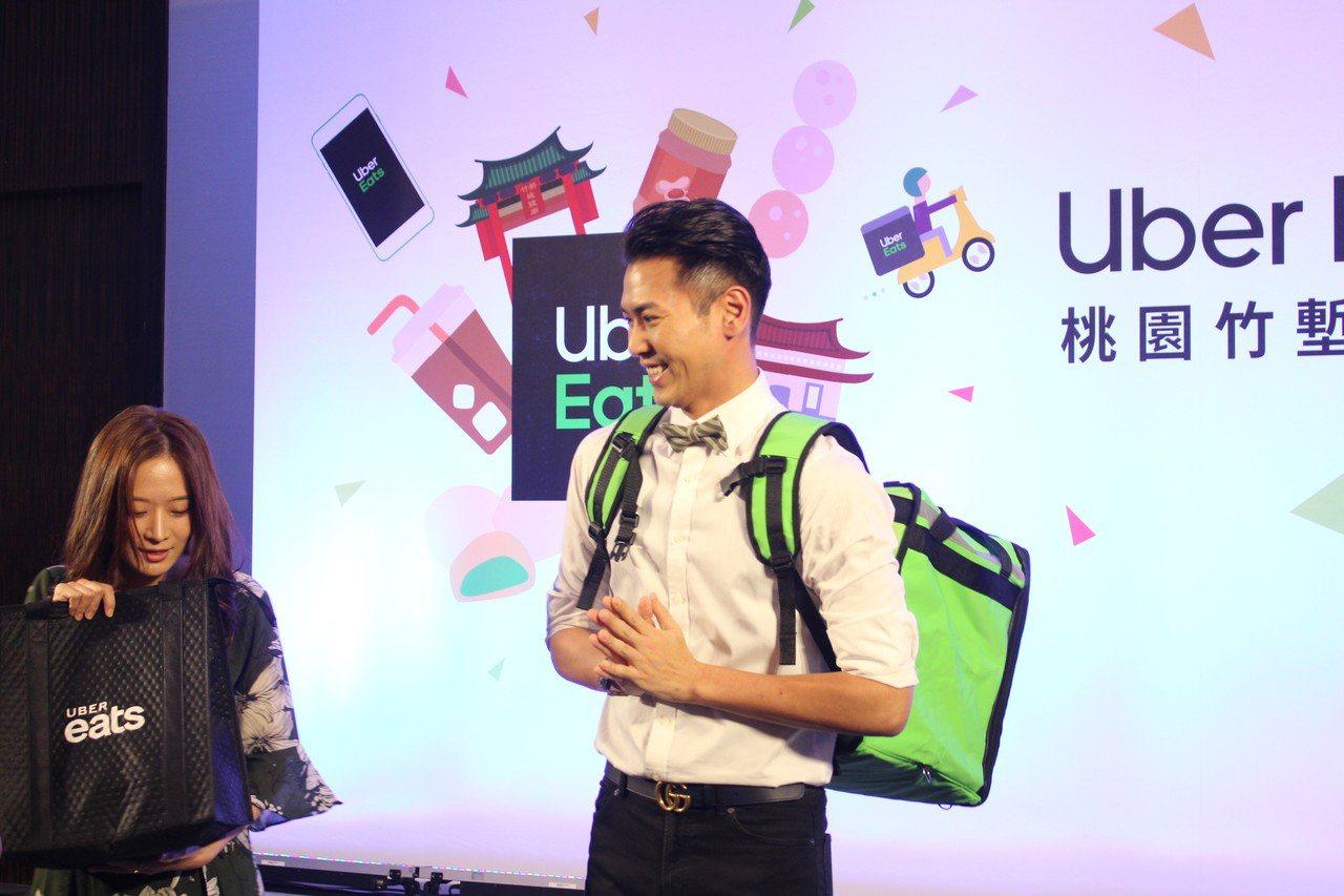 藝人陳德烈(右)今天當Uber Eats外送員,將小籠包等餐點外送到記者會場。記...