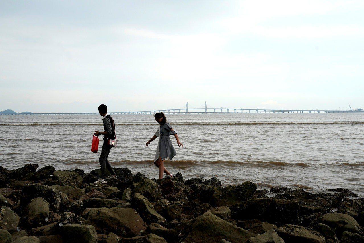 從兩名遊客的頭頂遠望是即將通車的港珠澳大橋。路透