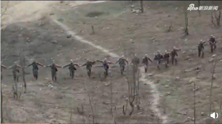日前,大陸網站上出現一段影片,內容為士兵們清除地雷後,手拉手踏進地雷區證明排雷成...