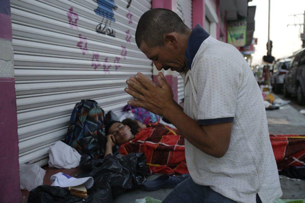 圖為一名中美洲移民在休息醒來後跪地祈禱畫面。 (美聯社)