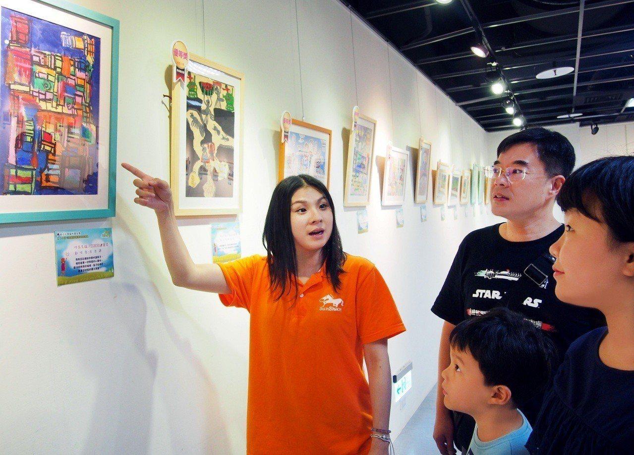 民眾在中壽志工熱情講解下,透過畫作更認識心智障礙者的內心世界。 中壽/提供