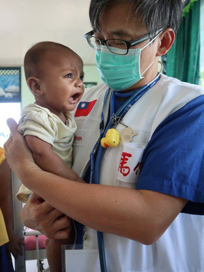 團長楊俊仁醫師抱著娃兒充滿不捨之情。 圖片提供/馬偕紀念醫院