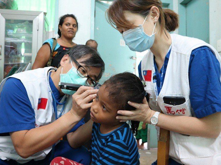 楊俊仁醫師(左)在簡單的環境下為吉國兒童看診。 圖片提供/馬偕紀念醫院