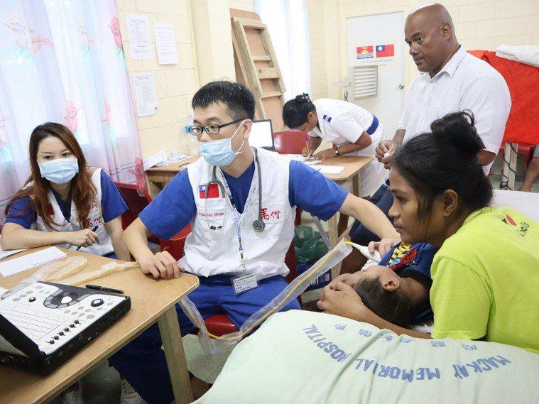 心臟內科林肇鋒醫師(右)在超音波檢查時同時請當地醫護人員翻譯說明。