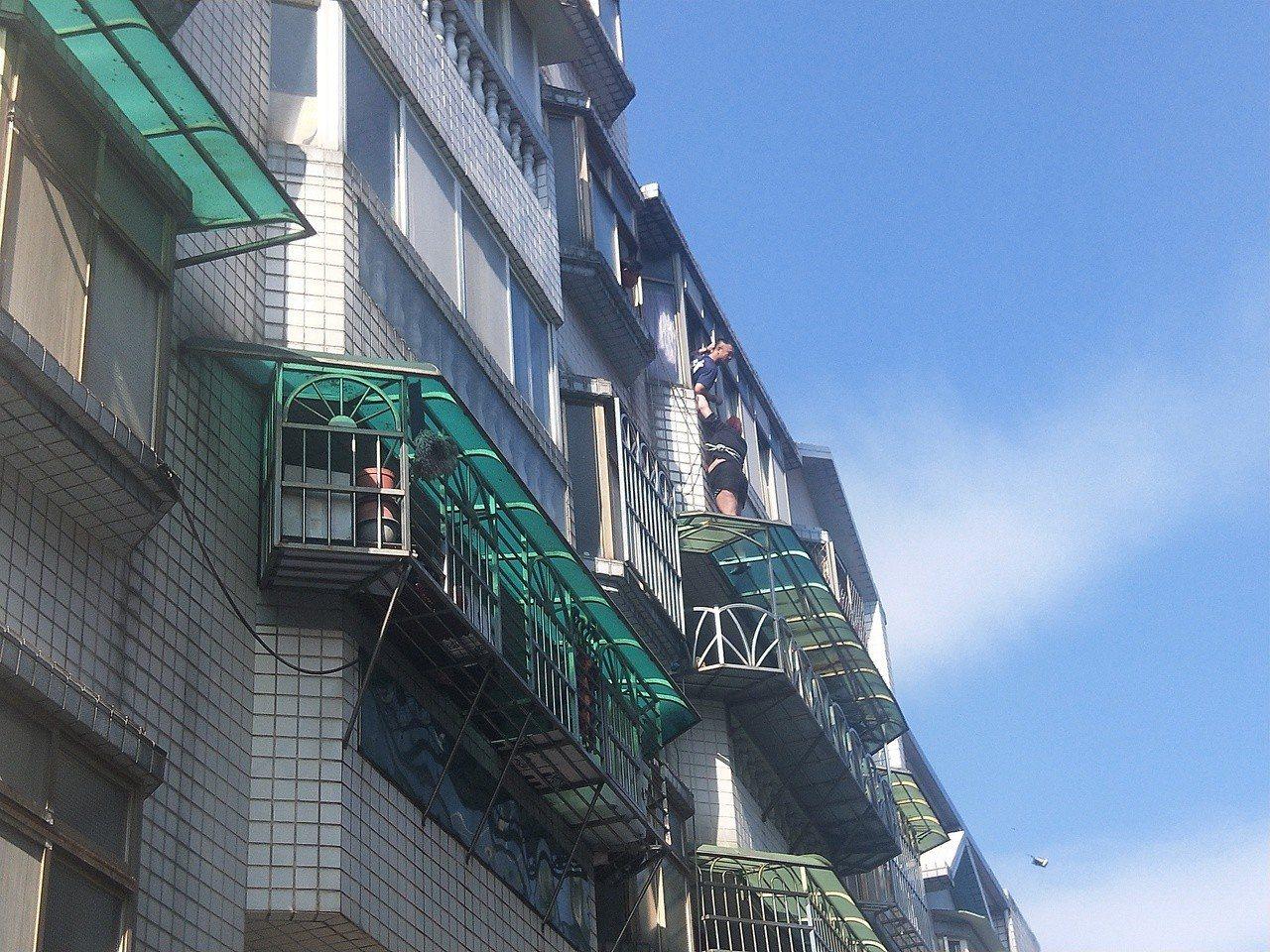 基隆市李姓婦人受困在4樓遮雨棚,消防人員驚險救援。記者游明煌/攝影