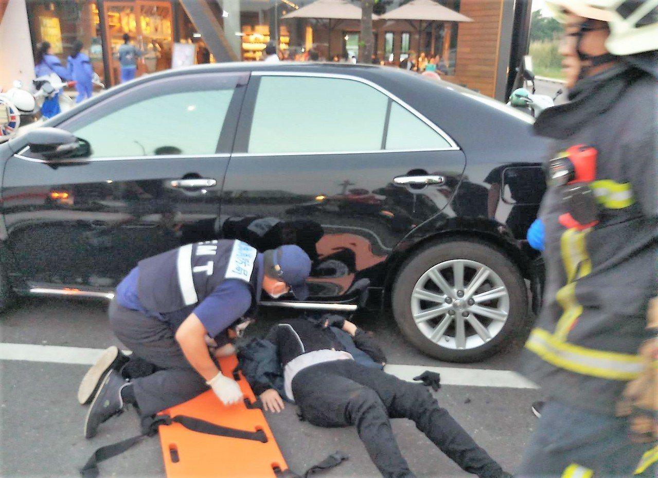 女子被噴飛摔在路旁一輛自小客車下,帶著安全帽的頭剛好卡在車底,就像被車子壓住。圖...