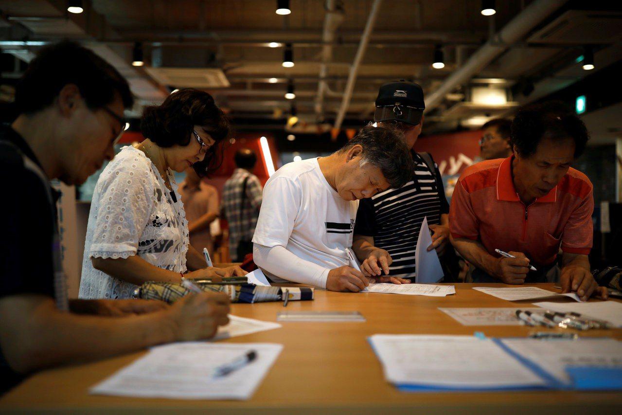 南韓參加就業展的求職者填寫表格準備面談。 路透