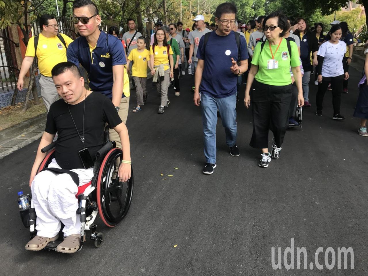 罕病友劉家幗(左一)以自身力量一馬當先的推著輪椅向前走著,偶爾才需親友協助,更是...