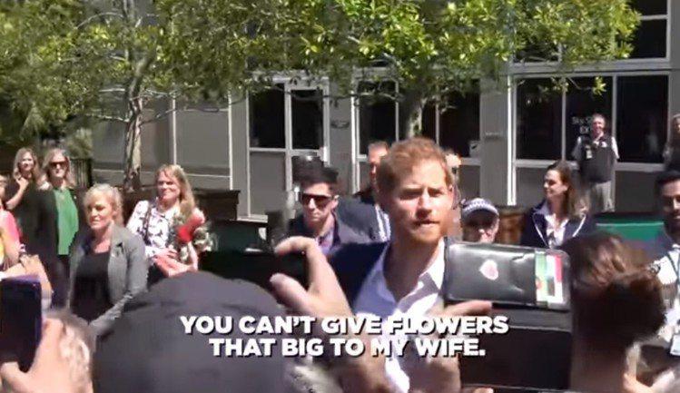 民眾送上超大把的花束給梅根,哈利故作吃醋警告對方。圖/摘自Youtube