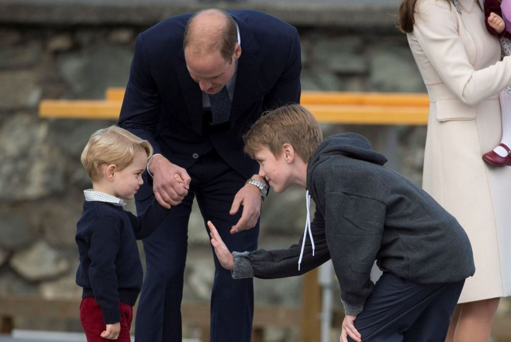 3歲的喬治在加拿大害羞拒絕與一名少年擊掌。(美聯社)