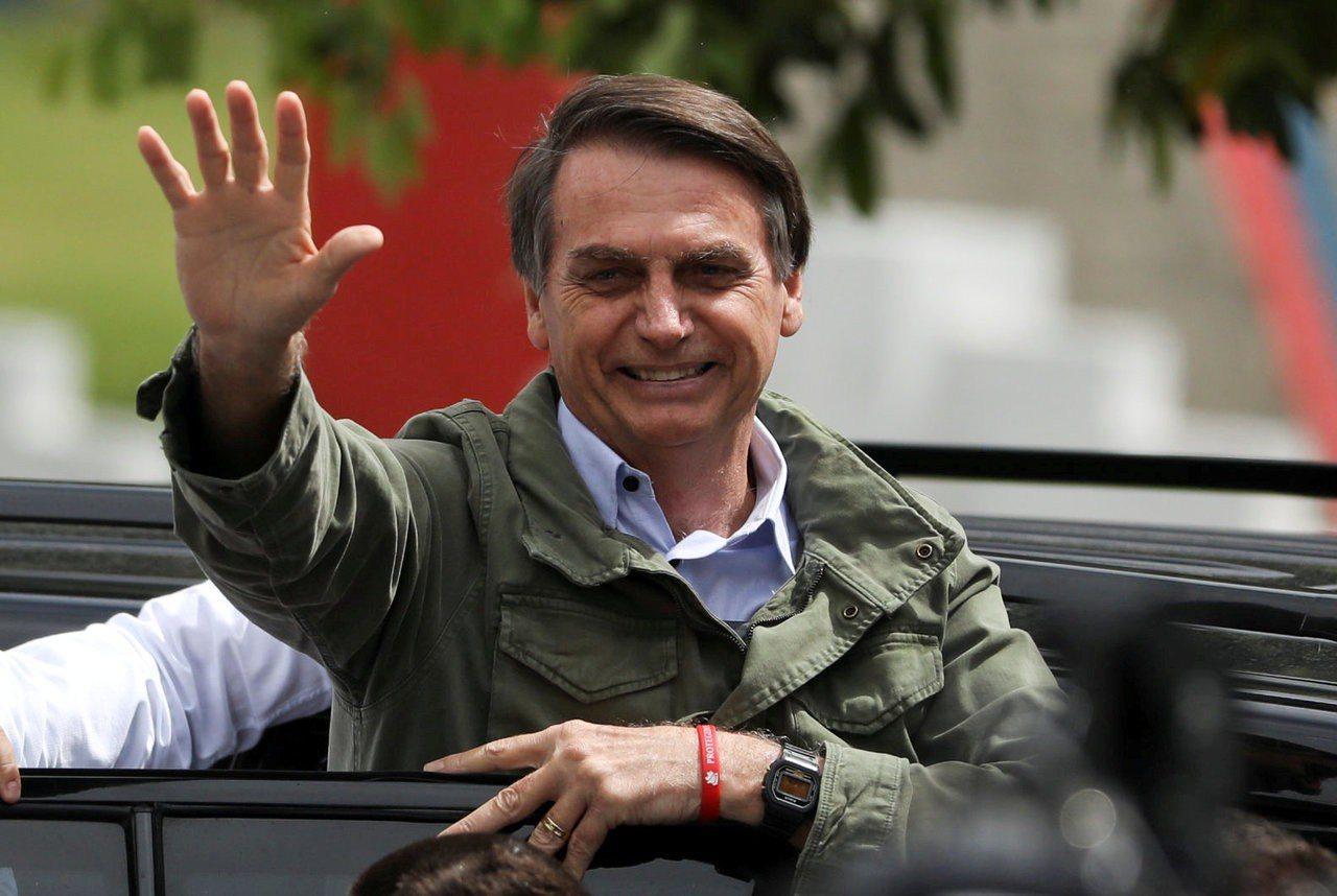 巴西極右派候選人波索納洛確定當選總統。圖為他28日在一間投票所外向支持者揮手。路...
