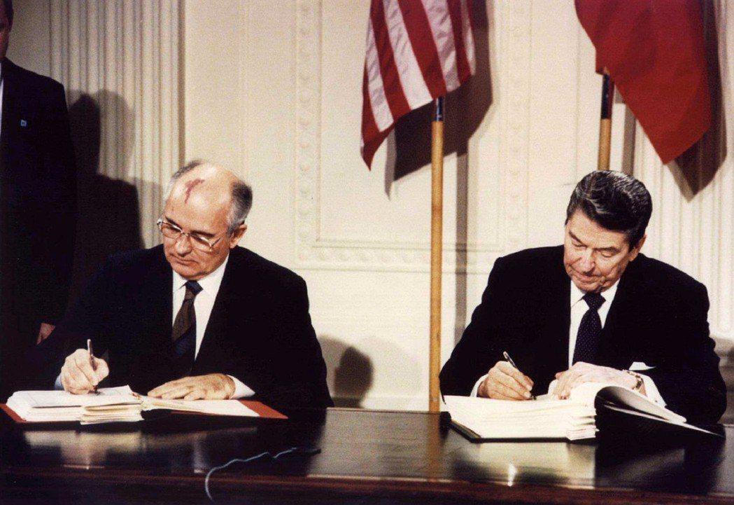 1987年,美����y雷根(右)和�K��I��人戈巴契夫(左)在白�m�署《中程核武�l�s...
