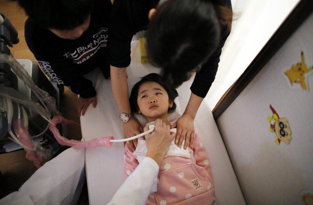 2014年,一名醫生正在對五歲女童進行甲狀腺檢查。 圖/路透社