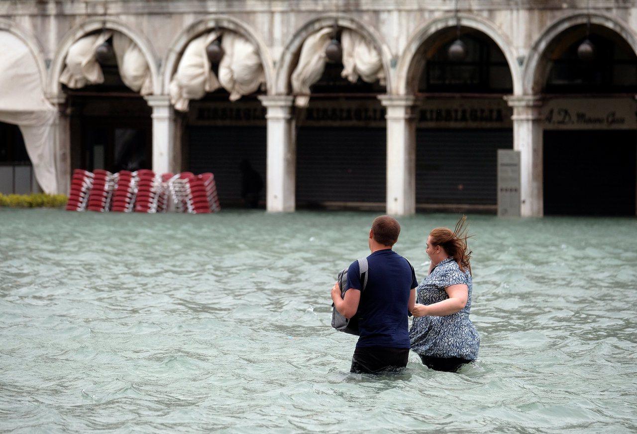 水淹威尼斯聖馬可廣場,一對情侶的下半身幾乎全浸在水中。路透