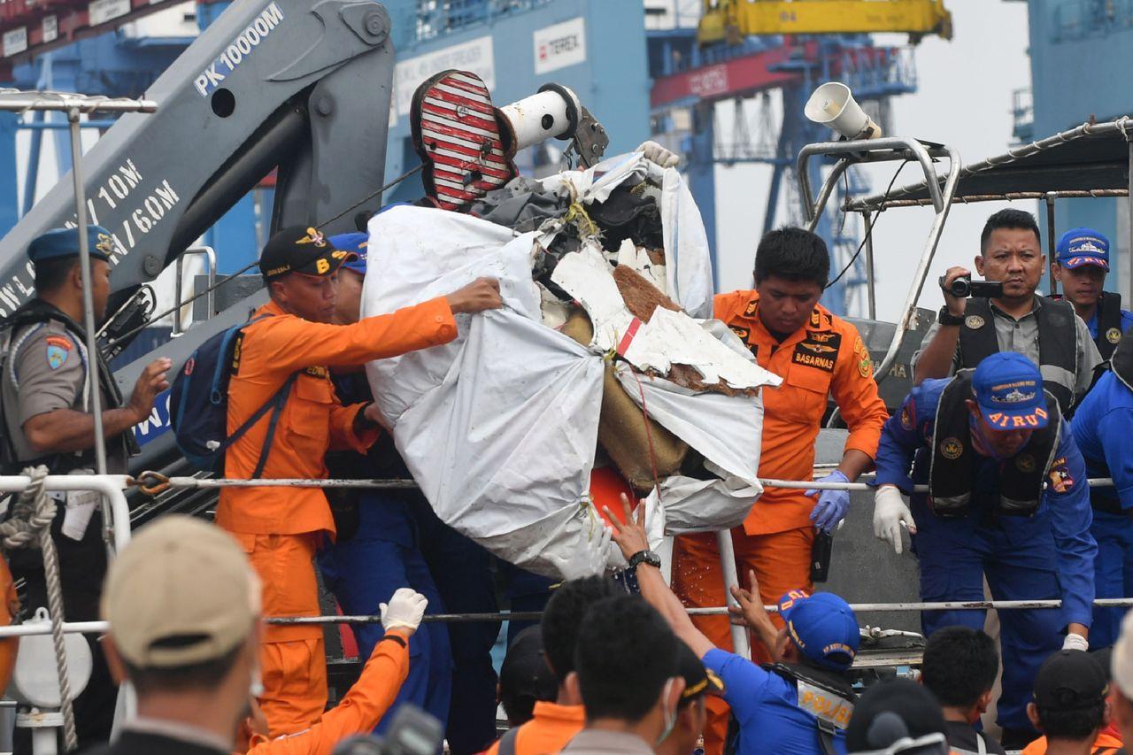 印尼搜救人員30日將打撈到的獅航失事客機殘骸從船上卸下。(法新社)