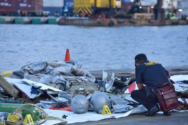 印尼鑑識人員仔細查看獅航飛機殘骸。 (法新社)