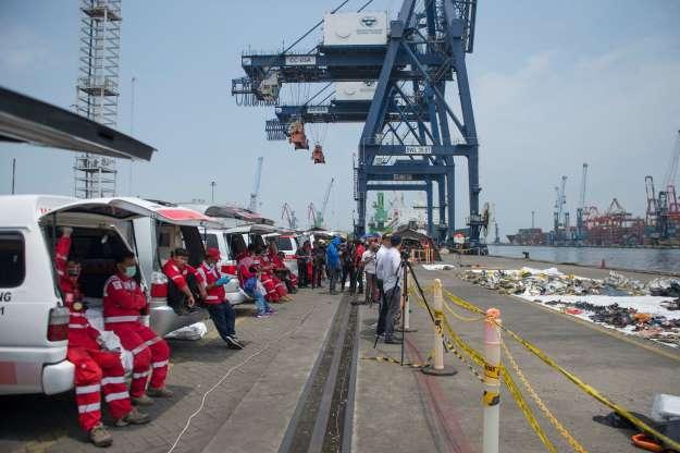 大批印尼救難人員在港口旁,等待尋獲上岸的獅航罹難者遺體。 (法新社)