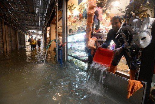 威尼斯的商家忙著把店內積水舀出屋外。 (歐新社)