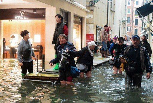 遊客走到臨時浮橋的盡頭,仍然得捲起褲管踏進及膝的積水中。 (法新社)