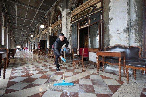 知名的福里安花神咖啡館門口,一名員工正賣力掃除積水。 (美聯社)