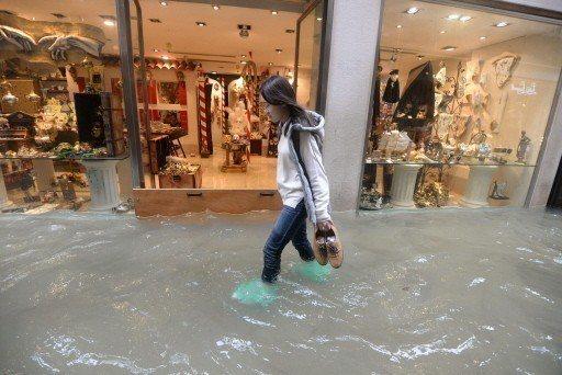 一名女子在威尼斯市區拎著鞋涉水前行,旁邊的服飾店門口架起閘門擋水。 (美聯社)
