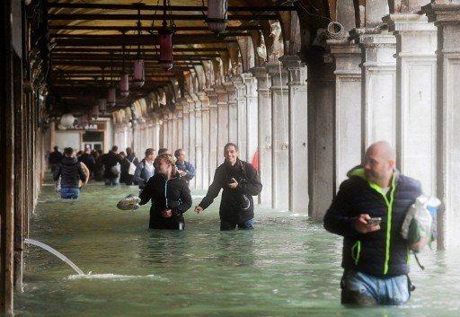 造訪威尼斯的遊客在水深及臀的積水中奮力前進。 (法新社)